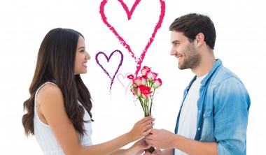 Happy hipster giving his girlfriend roses against valentines love hearts