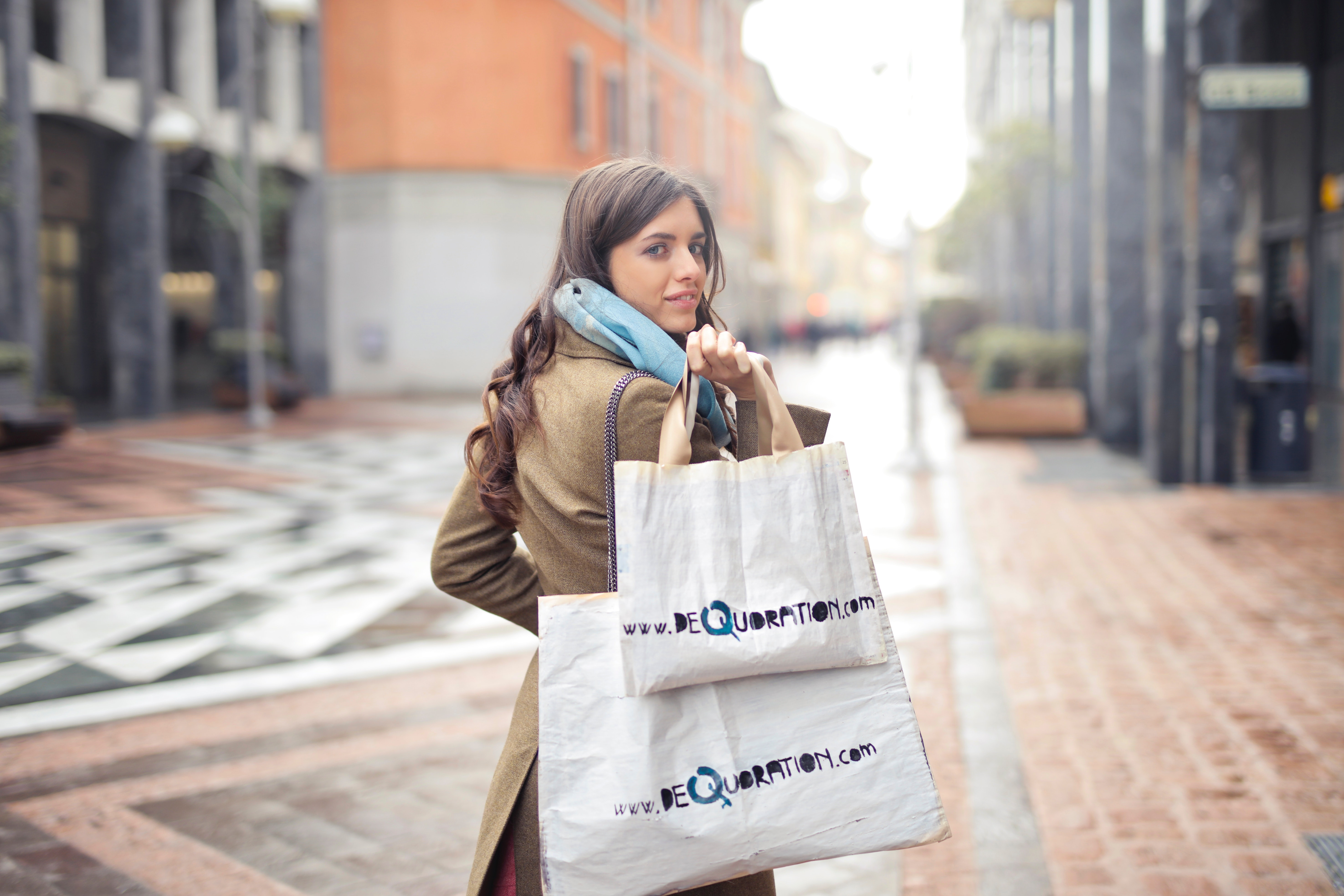 woman-in-brown-coat-carrying-two-white-tote-bags-919453