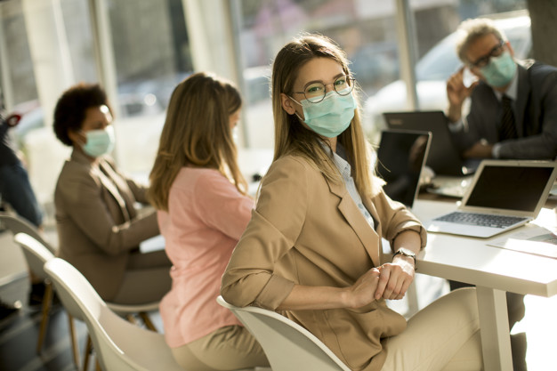 Pretty young woman and group business people have a meeting and working in the office and wear mask as protection from corona virus