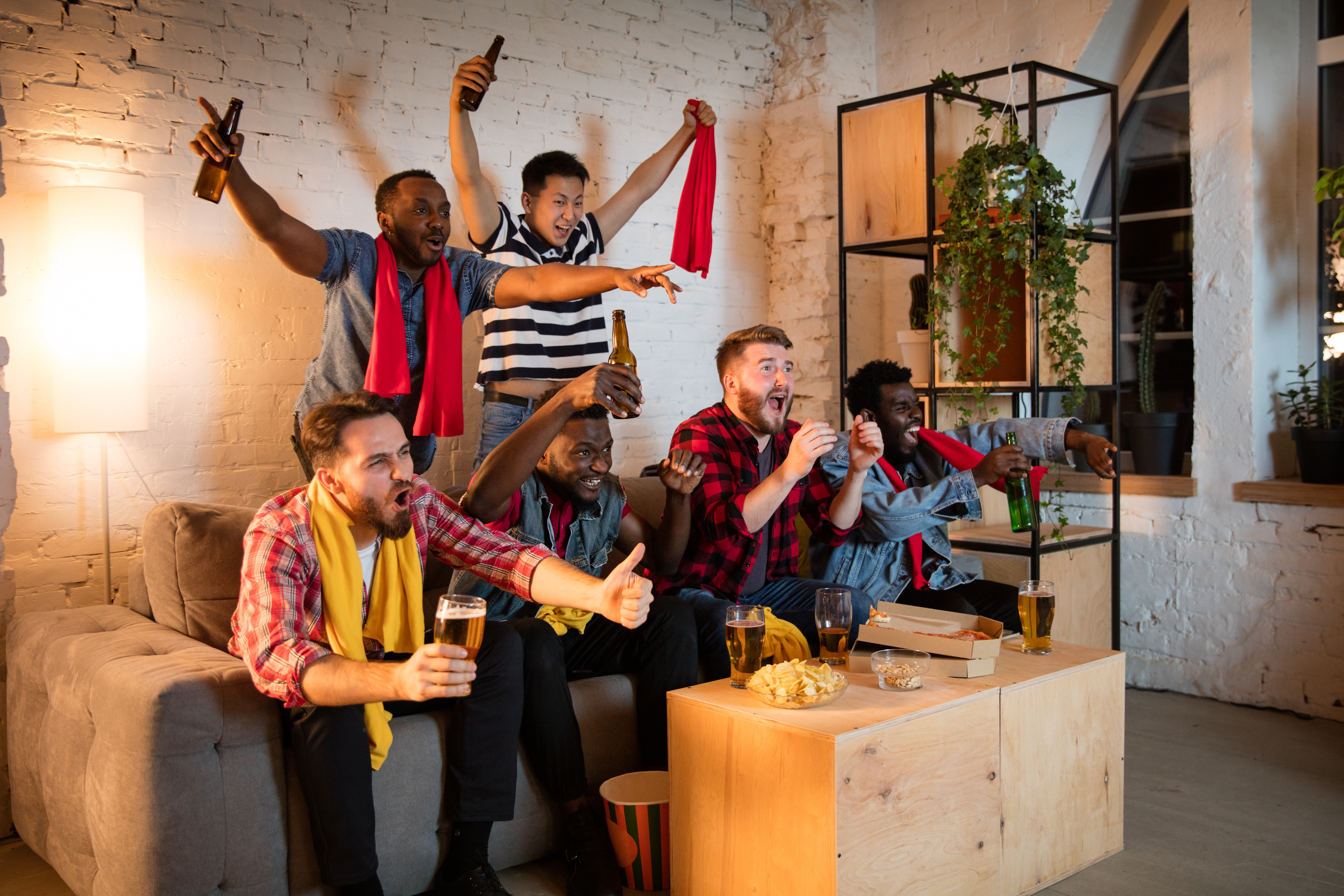 Group of friends watching TV, sport match together. Emotional fans cheering for favourite team, watching on exciting game. Concept of friendship, leisure activity, emotions