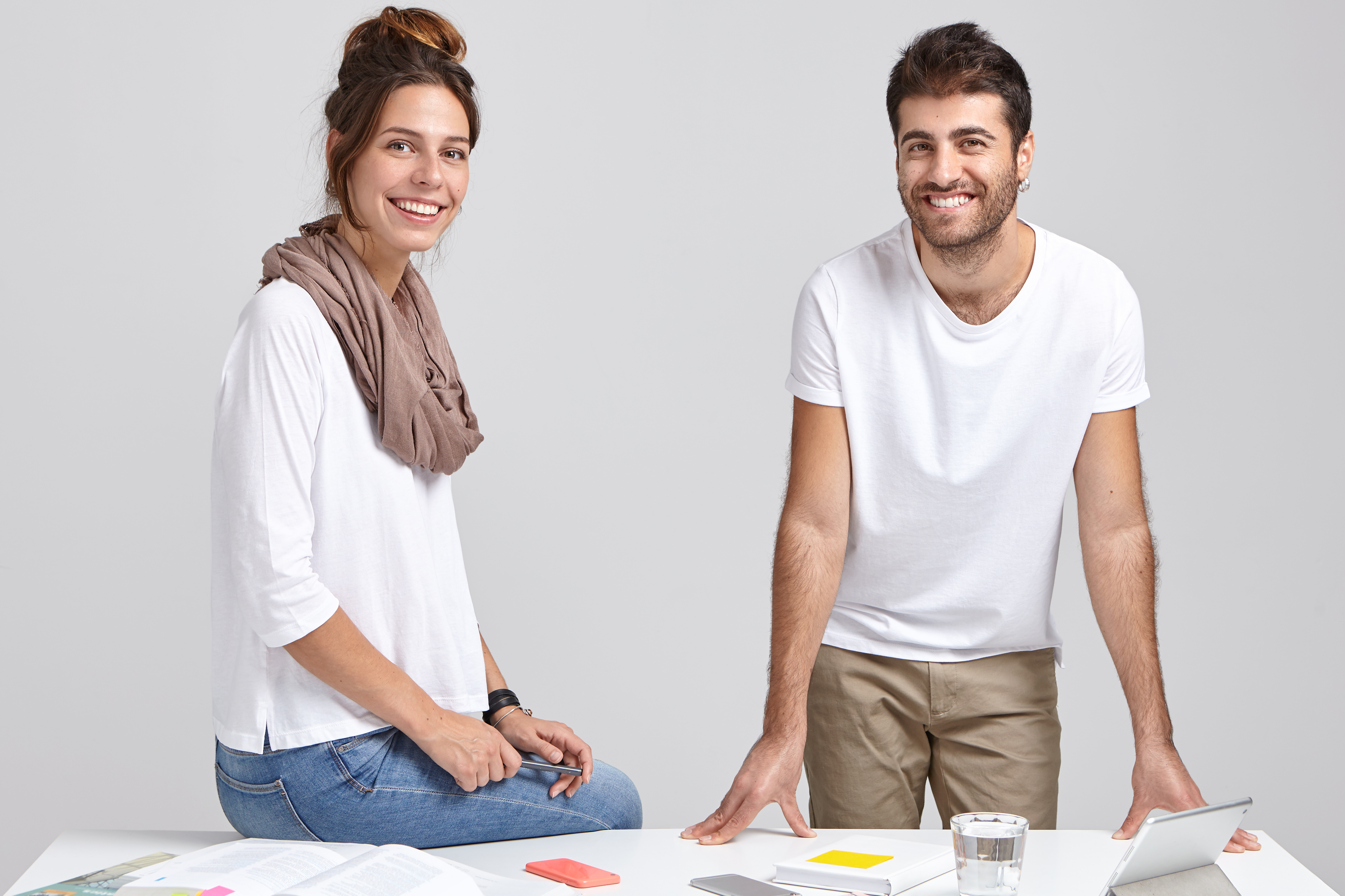 Image of woman and man architects collaborate together for common project, satisfied with productive work. Pretty lady in white jumper, scarf around neck sits at desk works with handsome guy