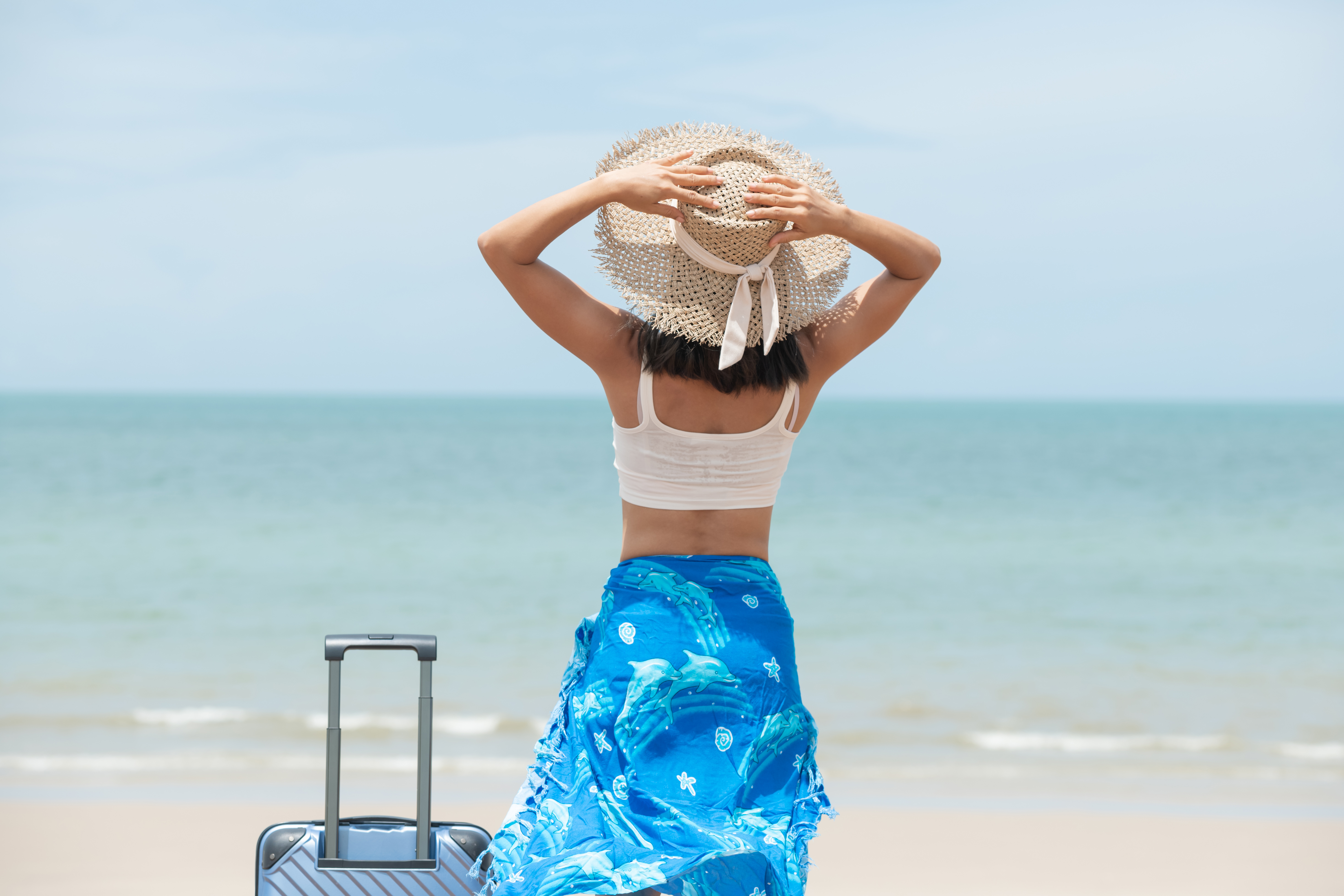 Beautiful young woman with a hat standing with suitcase on the w