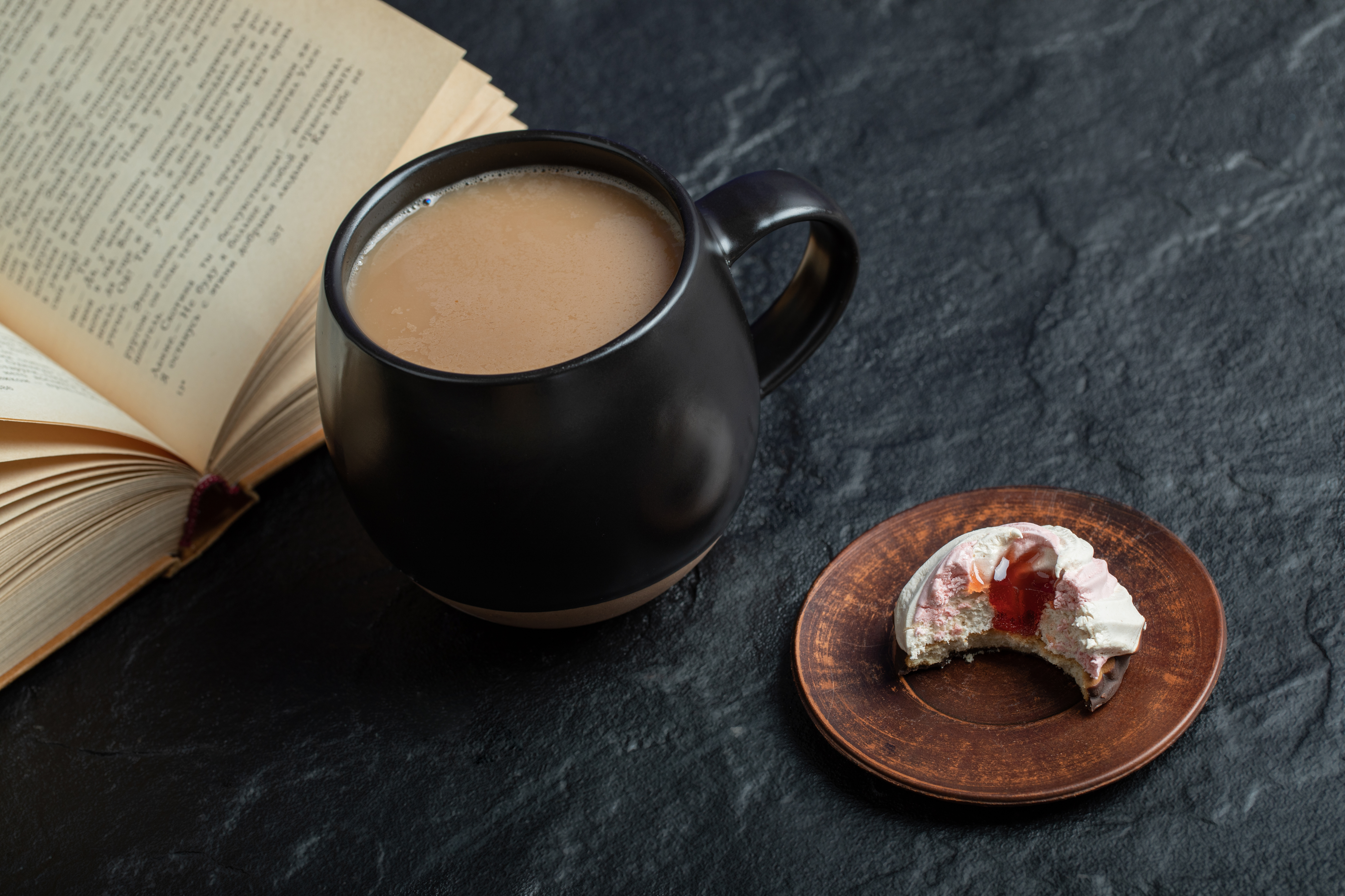 A cup of coffee with book and bitten cupcake