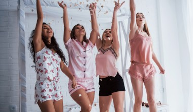 Raise up hands as high as possible Confetti in the air. Young girls have fun on the white bed in nice room