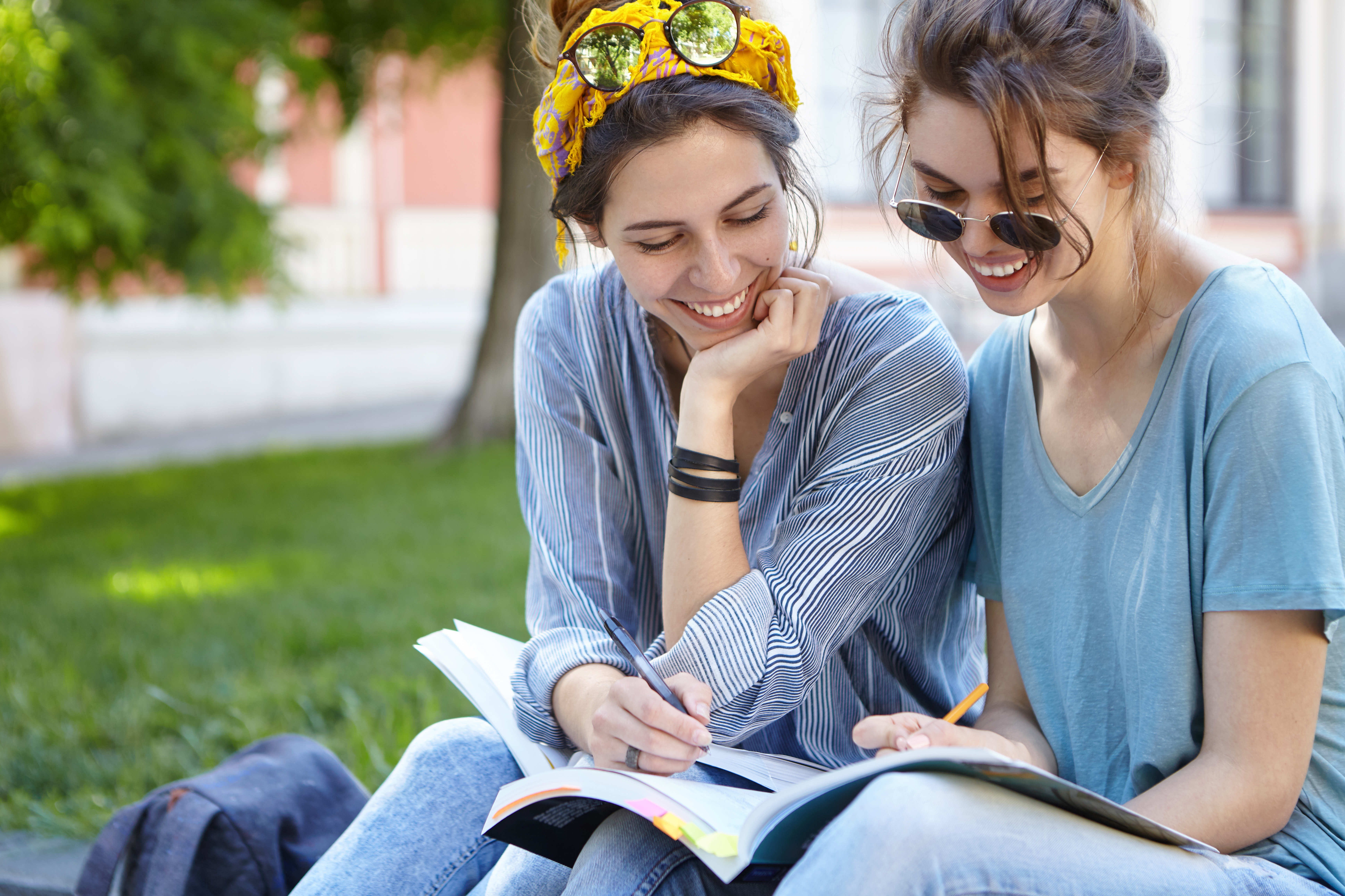 Happy smiling females sitting outdoors reading books preparing for classes at university having fun together admiring sunny weather and fresh air. Two beautiful women reading books in open air