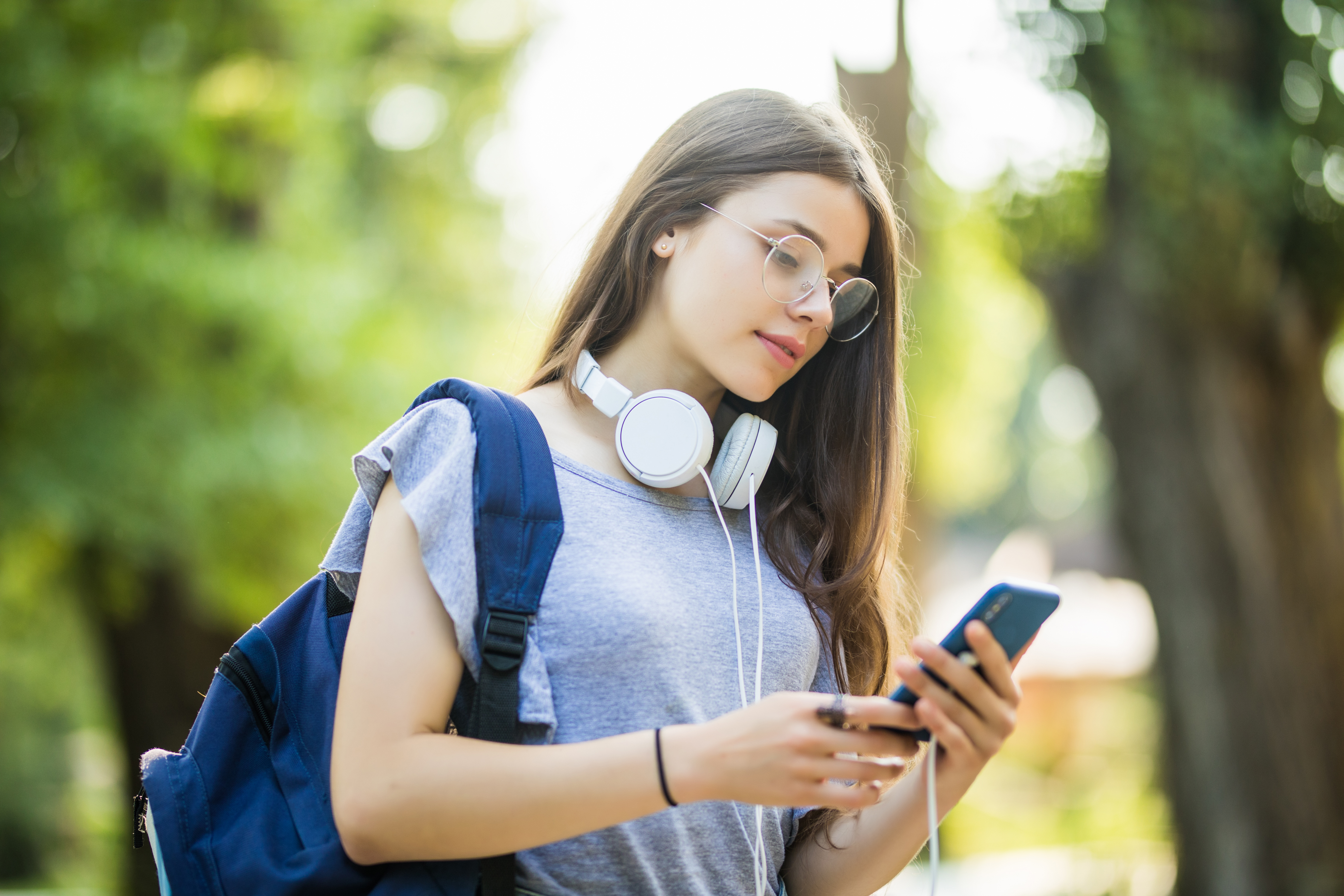 Happy beautiful young Caucasian girl with green smart phone outdoors on sunny summer day texting and smiling.