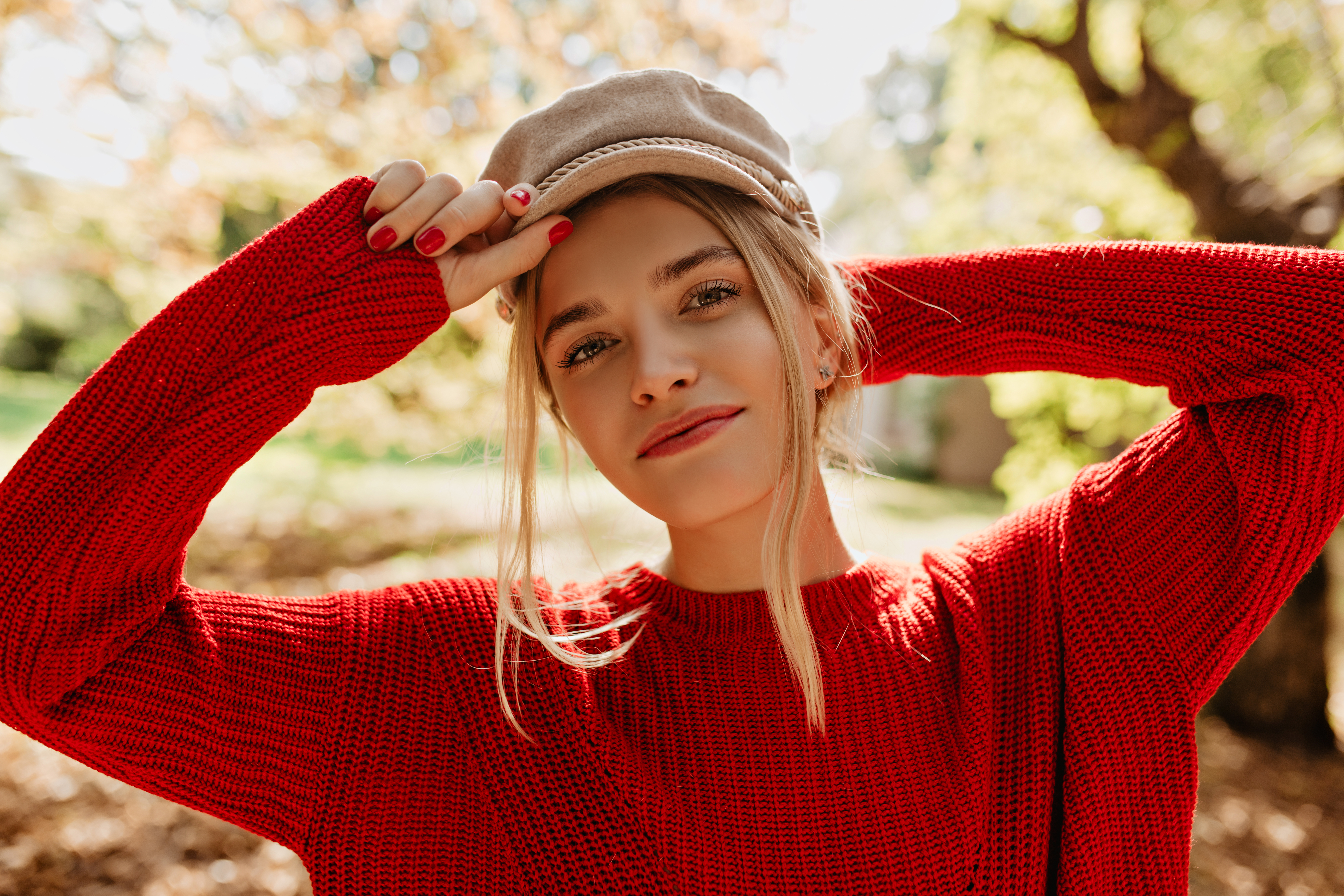 Charming girl in nice light hat and red sweater looking in the c